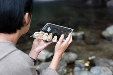 Asian woman eat sushi