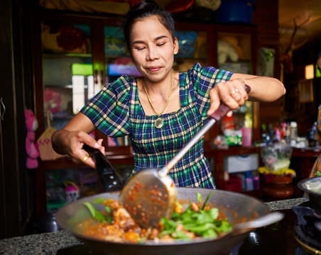 thai woman cooking traditional red curry in wok