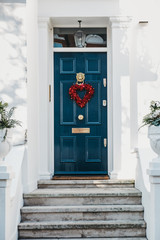 Blue front door with a red heart decoration on a facade of traditional English house in London, UK.