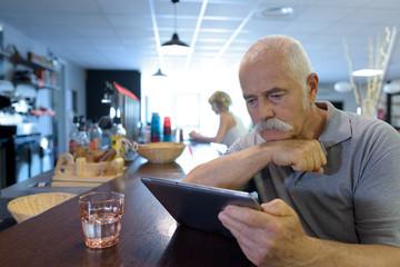 senior man sat at the bar looking at a tablet