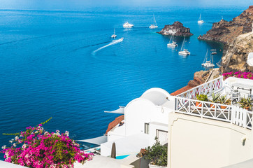 Oia Village, Santorini Cyclade islands, Greece. Beautiful view of the town with white buildings, blue church's roofs and many colored flowers.