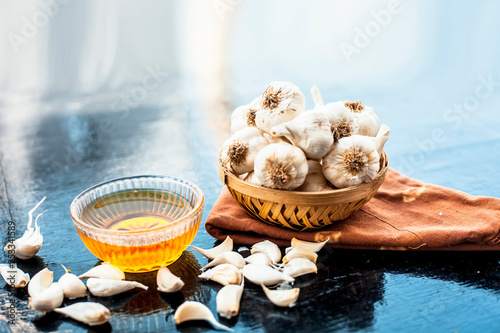 Raw garlic and honey with separate bowl on wooden surface