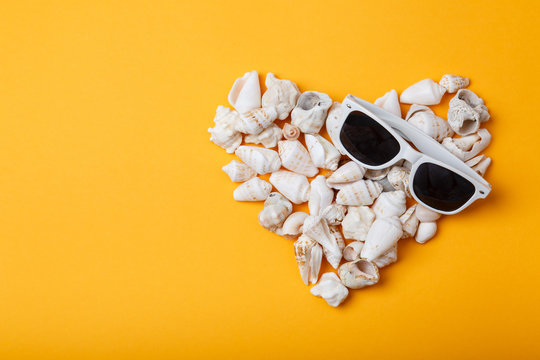Heart from seashells on orange background. Love summer. Sea holidays. Hot sunny background