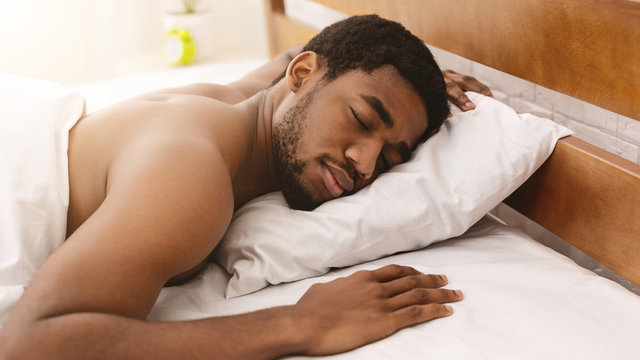 Naked african-american man sleeping in bed closeup