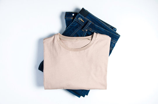 Skinny jeans and beige t-shirt on white background