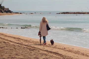 Woman with dog on walk on autumn beach. Santa Marinella, Italy