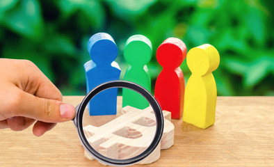magnifying glass is looking at Four multi-colored figures of people surround a bitcoin figure. Conceptual conduct of activities around cryptocurrency and blockchain technology. Selective focus