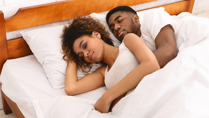 Loving couple sleeping in bed and hugging