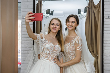 Friends in wedding dresses making selfie in salon