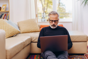 Senior man sitting using a laptop at home