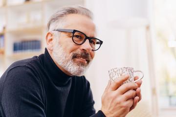 Thoughtful man enjoying a mug of tea or coffee
