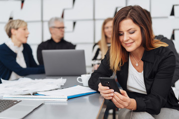 Woman smiling as she uses a mobile in a meeting