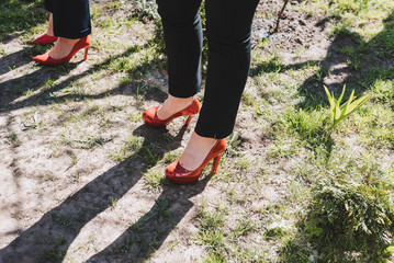 Women wearing black pants and red high heeled shoes standing on the ground