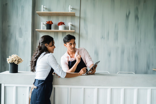 two waitress look serious to see the digital tablet while standing behind table bar in the cafe