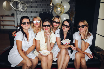 Cheerful bridesmaids and pretty bride wearing glasses, eating popcorn and watching film. Cheerful girl in white dresses looking at camera and posing. Young women celebrating wedding day.