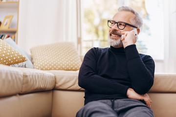 Senior man talking on his mobile phone at home