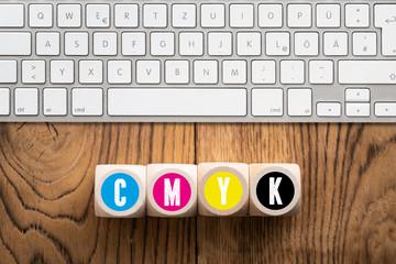 """Wüfel mit Buchstaben """"CMYK"""" vor Computertastatur"""