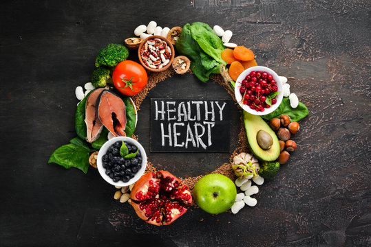 Healthy food for the heart: Fish, blueberries, nuts, pomegranate, avocados, tomatoes, spinach, flax. On a dark background. Top view. Free space for your text.