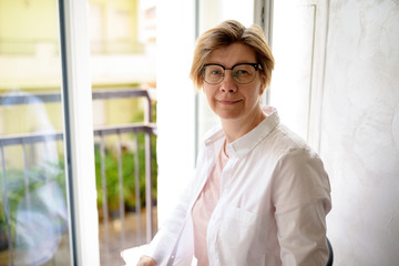 Portrait of pretty middle-aged woman in a white shirt, open window. Positive smiling woman with glasses.