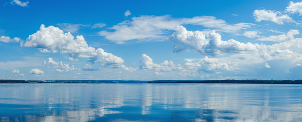Panorama of calm lake, Kama river blue sky with clouds reflected in the water. Wall mural