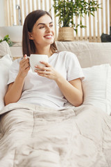 Woman sitting at the bed with a cup of coffee and looking to the window