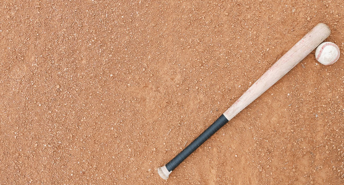 Horizontal image of old baseball bat with ball on dirt field.  Copy space beside sports equipment.