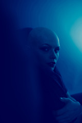 Emotive photo of a bald woman while sitting on a chair