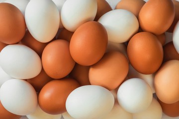 many beautiful delicious bright chicken eggs of orange and white color lying on top of each other
