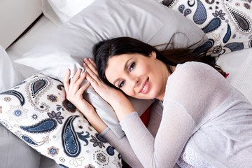 Portrait of a smiling pregnant woman lying on a bed