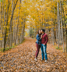 Man kissing happy woman while standing on dry leaves in forest during autumn