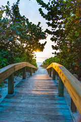 Wooden boardwalk in Naples beach entrance at sunset