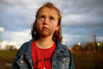 Sad thoughtful girl looking away while standing against cloudy sky during sunset