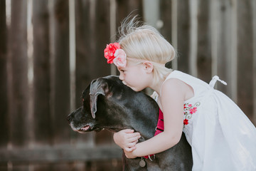 Side view of cute girl kissing dog while standing against fence in yard