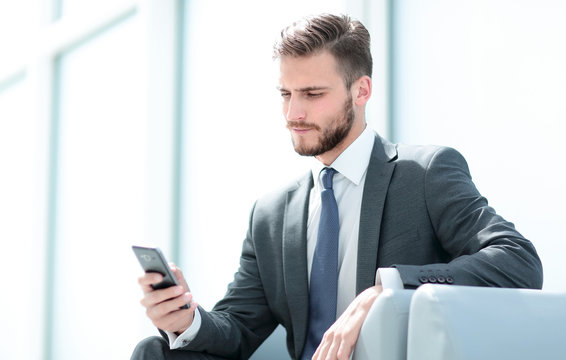 businessman sitting in an armchair with phone