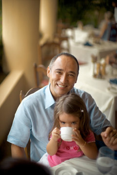 A small girl enjoys the drink as she is seated on her fathers lap.