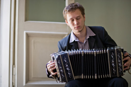 Young adult man sitting on a chair playing an accordion.