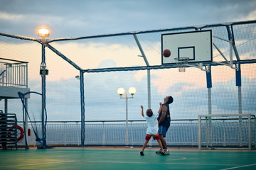 Man watches as a boy throws a basketball at the hoop on a fenced seaside basketball court.