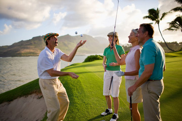 Male golfer smoking a cigar juggles golf balls for his friends as they take a break together.