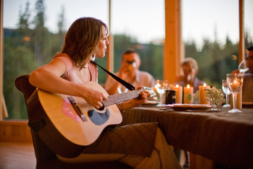 Woman playing guitar for family at dinner table