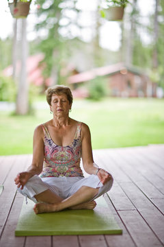 Mature woman meditating while doing yoga on a porch.