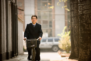 Portrait of a mid-adult businessman riding a bicycle down a street.