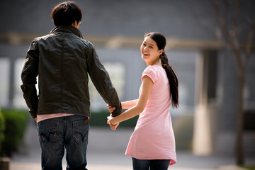 Portrait of a young couple holding hands walking through a park.