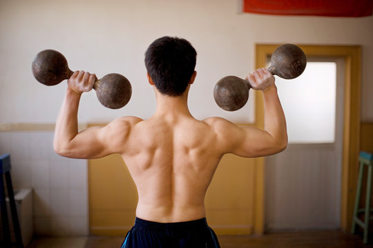 Young adult boy lifting dumbbells in a gym.