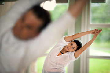 Middle-aged woman stretching her arms above her head in a relaxing yoga class at a health spa.