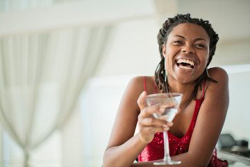 Smiling young woman enjoying a cocktail at a bar.