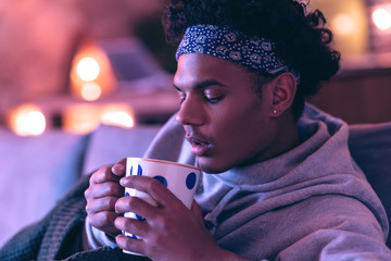 Handsome African American guy sniffing fresh herbal infusion from a cup.