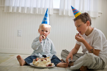 Two young boys eating a cake that has been squashed