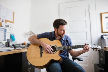 Young adult man playing an acoustic guitar in a home office.