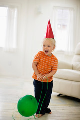 Toddler wearing a party hat with a balloon.