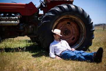 Man asleep against tractor in field